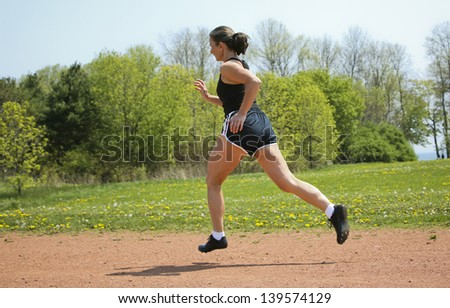 mature woman running outdoors in the park - stock photo