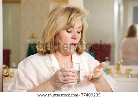 Mature woman's morning routine - holding medicine and water - stock photo