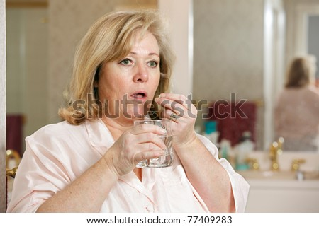 Mature woman's morning routine - taking medicine with glass of  water - stock photo