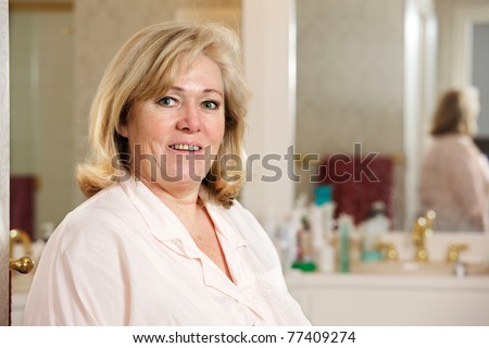 Mature woman's morning routine - today's going to be great! - stock photo