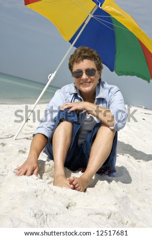 Mature woman seated on a white sandy beach enjoying the whole experience.