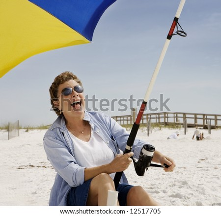 Mature woman seated on the beach fishing, at the moment she's got a bite! - stock photo