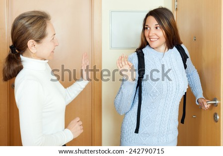 Mature woman sees off his young daughter at the door from home - stock photo
