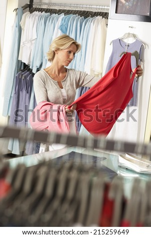 Mature woman shopping in clothes shop, holding red vest top, thinking, focus on background (tilt) - stock photo