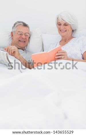 Mature woman showing her book to husband in bed - stock photo