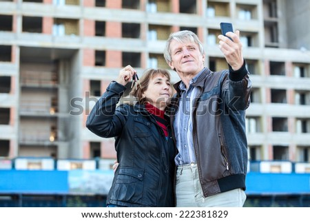 Mature woman showing house key when husband making selfie - stock photo