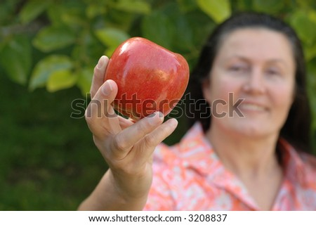 Mature woman showing off an apple in her garden; senior healthy lifestyle concept - stock photo