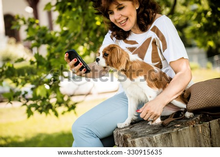Mature woman showing something to her  cavalier dog on smartphone, outdoor in nature - stock photo