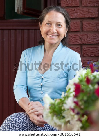 Mature woman sits on   porch of  house in village.