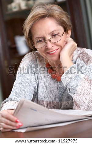 Mature woman sitting and reading newspaper - stock photo