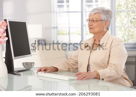 Mature woman sitting at table at home, using computer. - stock photo