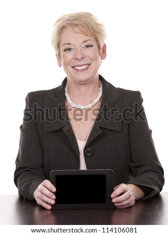 mature woman sitting behind desk and holding tablet - stock photo