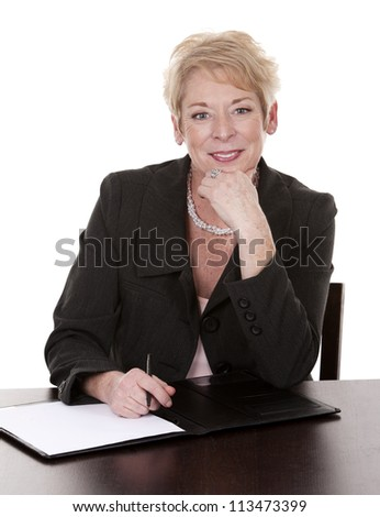 mature woman sitting behind desk and writing notes down - stock photo