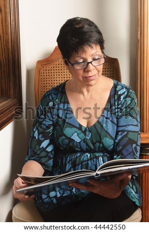 mature woman sitting by window looking at pictures in book - stock photo