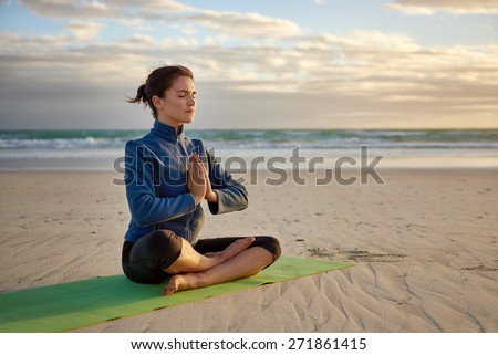Mature woman sitting in a cross-legged yoga pose on a deserted beach at daybreak, with her hands together in front of her chest, she is focused with her eyes closed - stock photo