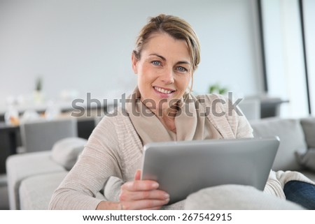 Mature woman sitting in sofa and websurfing with tablet - stock photo