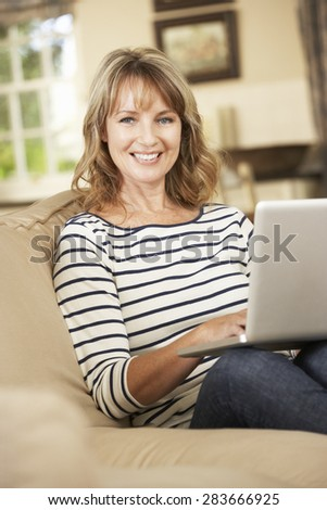 Mature Woman Sitting On Sofa At Home Using Laptop - stock photo