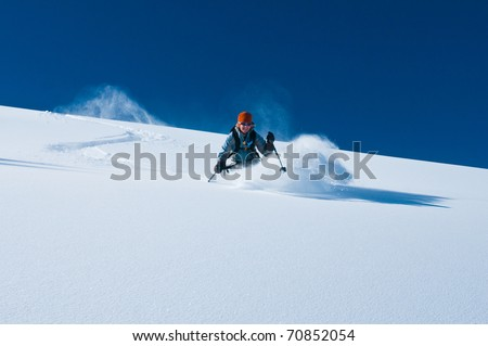 mature woman skiing un-tracked deep powder snow on bluebird day in aspen back-country - stock photo