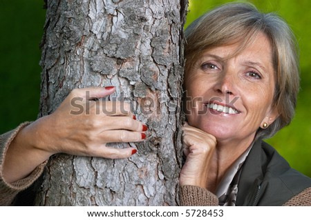 Mature woman smiles and embraces a tree. - stock photo
