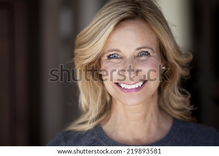Mature woman smiling at the camera - stock photo