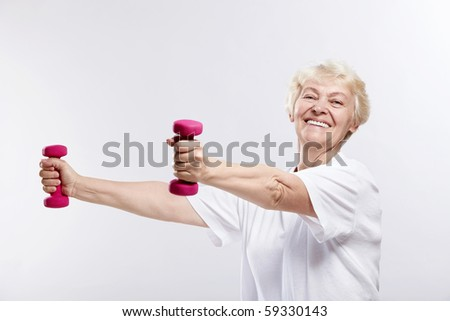 Mature woman smiling with dumbbells on white background