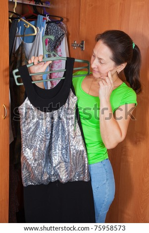 Mature woman standing at wardrobe. She thinking what get dressed - stock photo