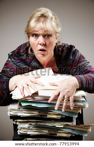 Mature woman struggles to control huge stack of paperwork - stock photo