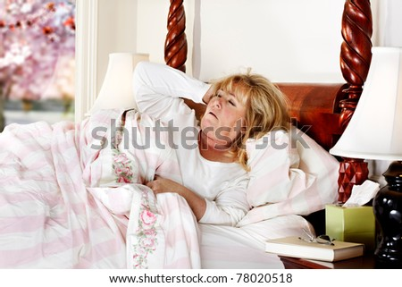 Mature woman struggles to wake up in the morning - stock photo