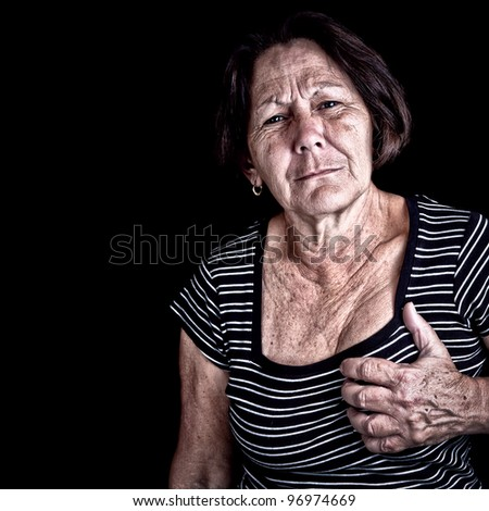 Mature woman suffering from chest pain or depression on a black background with space for text - stock photo