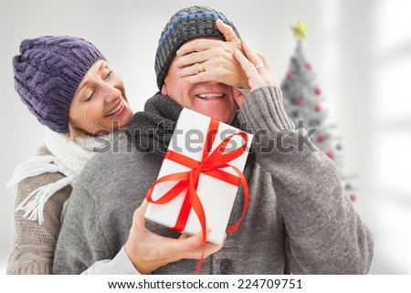 Mature woman surprising partner with gift against blurry christmas tree in room - stock photo