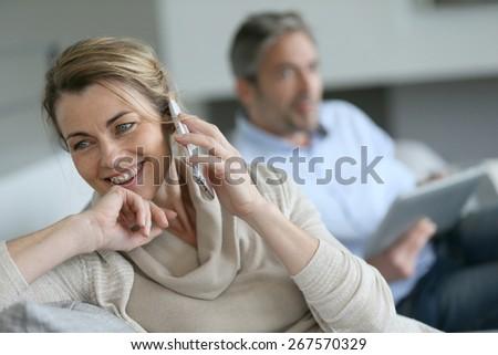 Mature woman talking on smartphone, husband using tablet - stock photo