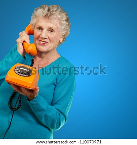 Mature Woman, Talking On Telephone On Blue Background - stock photo
