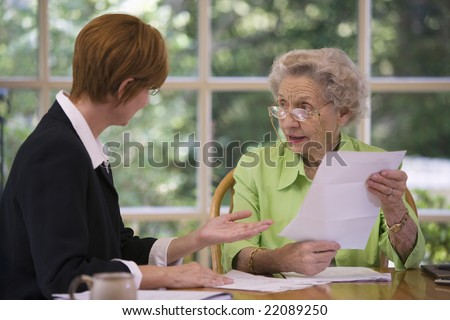 Mature woman talking to financial planner at home - stock photo