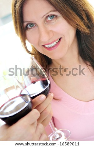 Mature woman toasting with a glass of red wine - stock photo