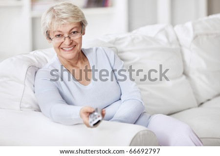 Mature woman TV remote control changes channels - stock photo