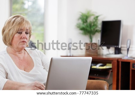 Mature woman typing on a laptop in her home office - stock photo