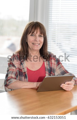 Mature woman using a tablet at home