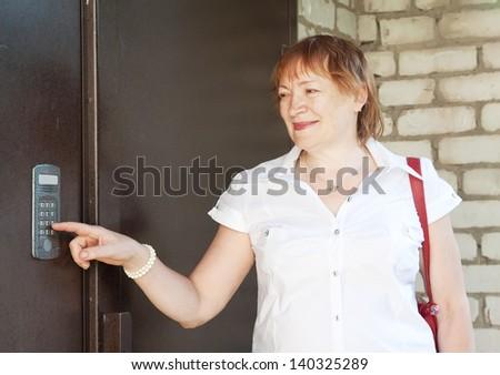 Mature woman using house intercom outdoor - stock photo