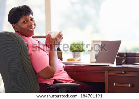 Mature Woman Using Laptop On Desk At Home - stock photo