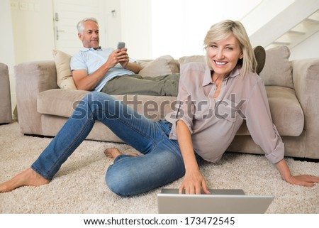 Mature woman using laptop while man text messaging in the living room at home