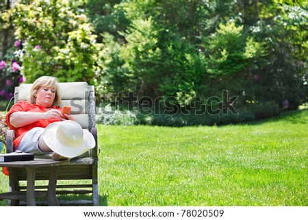 Mature woman using PDA while enjoying the Spring sunshine - stock photo