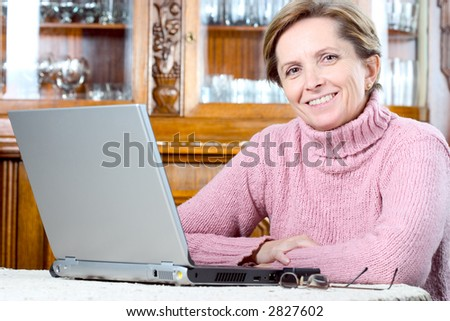 Mature woman using the laptop and smiles. - stock photo