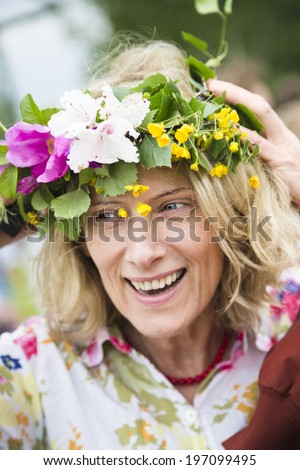 Mature woman wearing flower wreath, Nykoping, Sodermanland, Sweden - stock photo