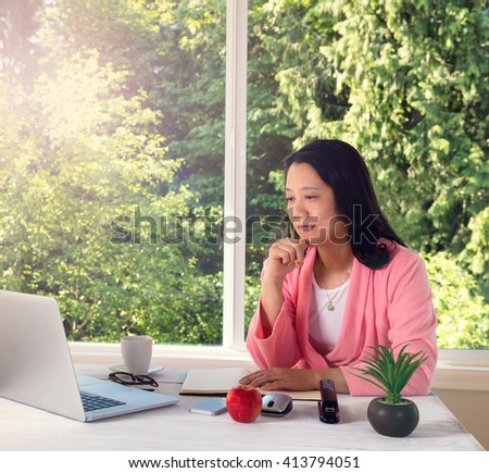 Mature woman, wearing pink bathrobe, working from home in front of large window with bright daylight and trees in background. Light haze effect applied to image.