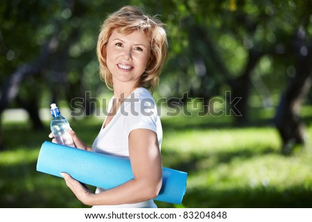 Mature woman with a gym mat and a bottle of water in the park - stock photo