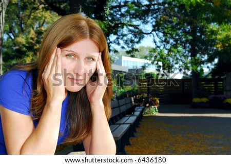 Mature woman with a headache sitting on the park bench - stock photo
