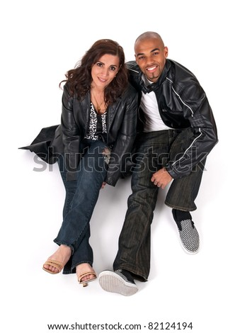 Mature woman with a younger man, sitting close to each other and smiling. - stock photo