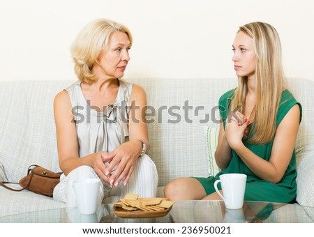 Mature woman with  adult daughter having serious conversation on sofa at home