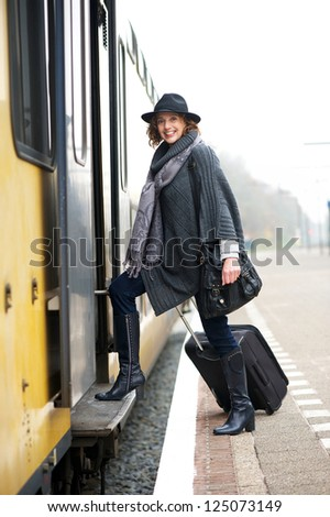 Mature woman with bag walking on to train - stock photo