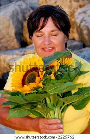 Mature woman with bouquet of sunflowers